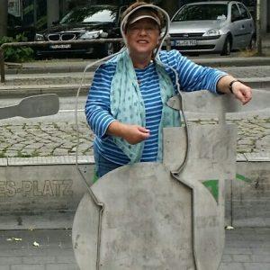 Touristin steht bei Stadtführung vor Metallskulptur in Hamburg
